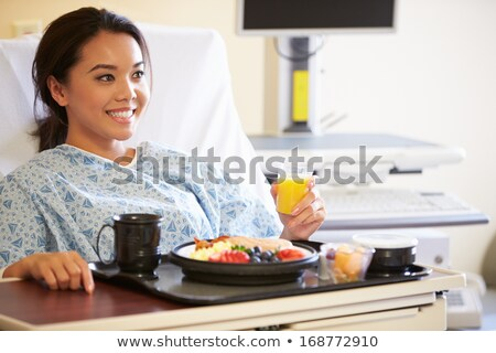 Patient in hospital lying in bed eating meal Stock photo © Kzenon