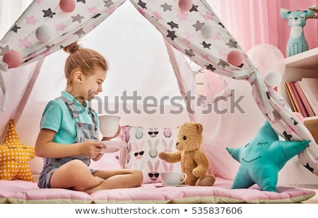 girl playing tea party with teddy in kids tent Stock photo © dolgachov