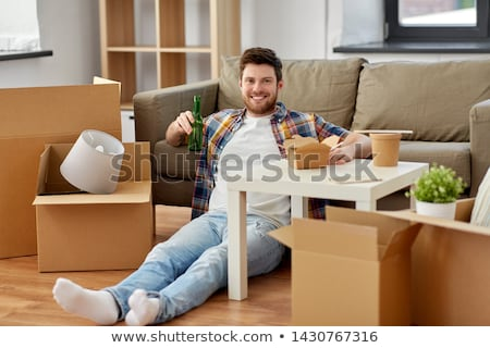 smiling man drinking beer and eating at new home Stock photo © dolgachov