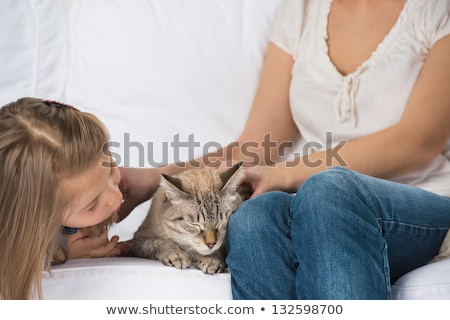Mother and daughter sitting on sofa and cuddling cat Stock photo © HASLOO