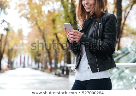 smiling woman standing and using mobile phone in park stock photo © deandrobot