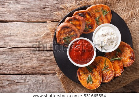 Stockfoto: Grilled Sweet Potatoes Served With Tomato Sauce Close Up On A Ta