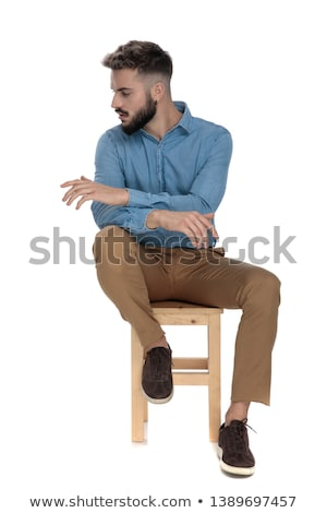 seated young business man sitting with hands crossed  looks away Stock photo © feedough