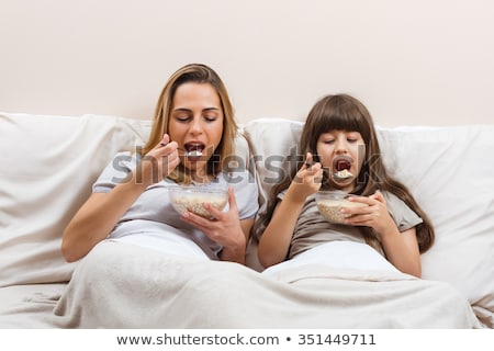 Two women sitting on bed eating cereal smiling stock photo © monkey_business