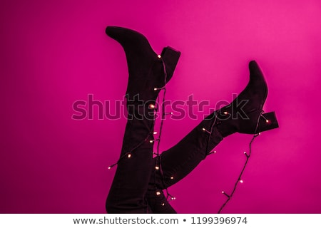 A slender girl in classic black high-heeled shoes and jeans holds in her hand with a pink rose tatto Stock photo © artjazz