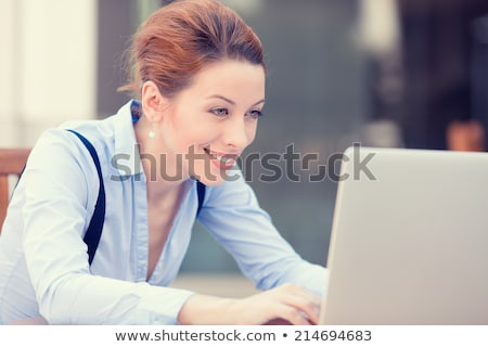 Successful businesswoman looking at computer Stock photo © Kzenon