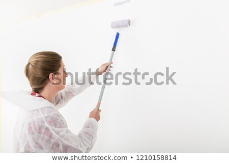Stock photo: Side view of woman painting with anchor roller