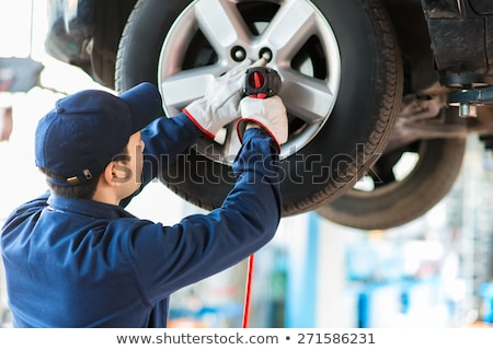 Stock photo: Mechanician changing car wheel in auto repair shop