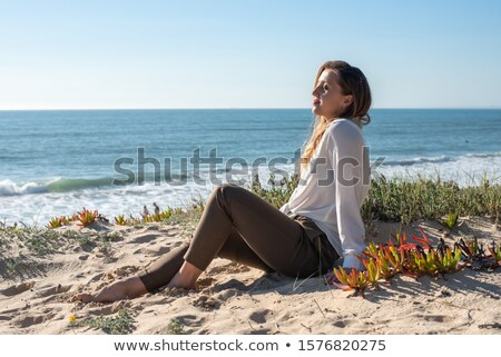 Young girl sitting on a sand dune Stock photo © iko