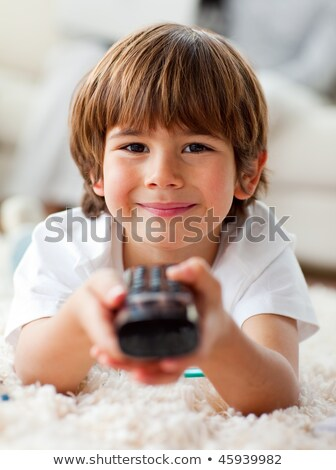 little boy watching tv lying in the living room stock photo © lopolo