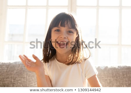 Portrait of Cute little child girl sitting on sofa in living room enjoy reading a big book Stock photo © Lopolo