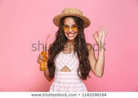 Image of pretty girl 20s wearing sunglasses drinking soda bevera Stock photo © deandrobot