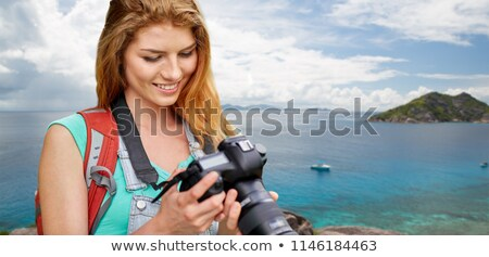 woman with backpack and camera over seychelles stock photo © dolgachov