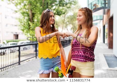 teenage girls with skateboards making fist bump Stock photo © dolgachov