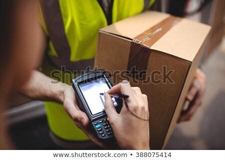 Mujer firma dispositivo entrega paquete mujeres Foto stock © Kzenon