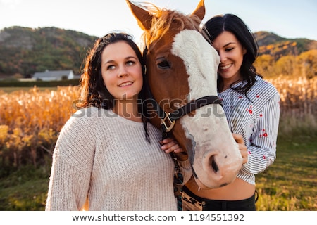 two womans with her horse at sunset autumn outdoors scene stock photo © lopolo