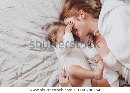 Foto stock: Top view of beautiful young mother and her daughter in bed at home