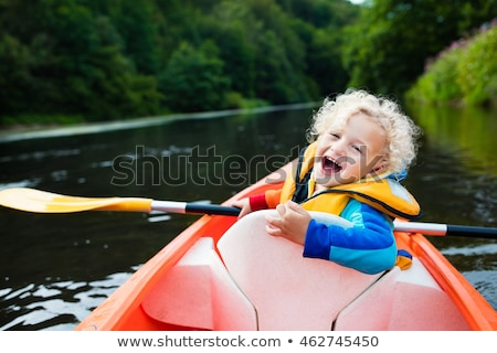 Happy kid enjoying canoe ride on beautiful river Stock photo © Lopolo