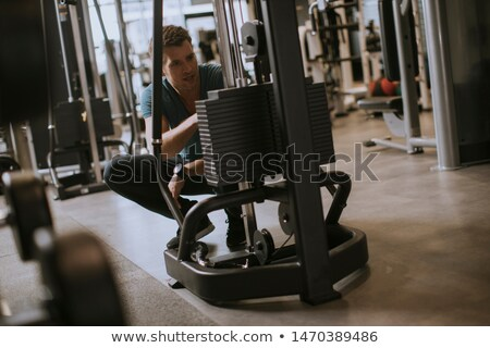 Athlete adding weight plates, preparing for his weightlifting wo Stock photo © boggy