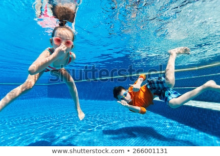 Kids having fun playing underwater in swimming pool on summer vacation Stock photo © galitskaya
