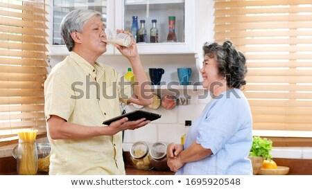Senior couple holding glass of milk Stock photo © Kzenon