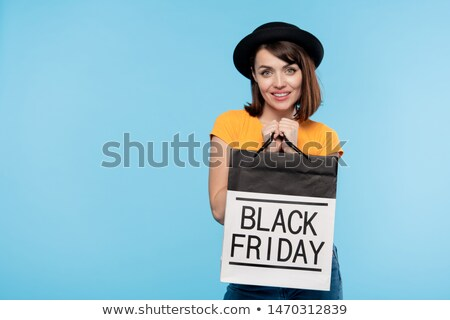 Happy young shopaholic holding paperbag while boasting with purchase Stock photo © pressmaster