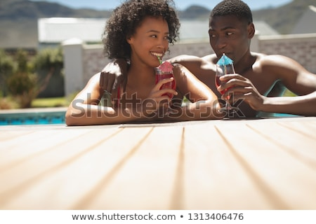 Front view of happy young African American couple leaning on edge of pool and drinking cocktail in t Stock photo © wavebreak_media