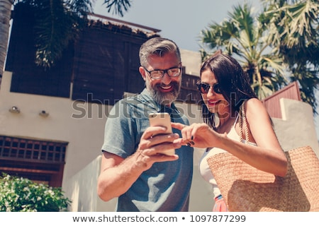 Two women in a bar looking at their mobile phone Stock photo © Kzenon
