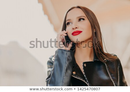 Headshot of pleasant looking dreamy woman focused aside, has telephone conversation, wears leather c Stock photo © vkstudio