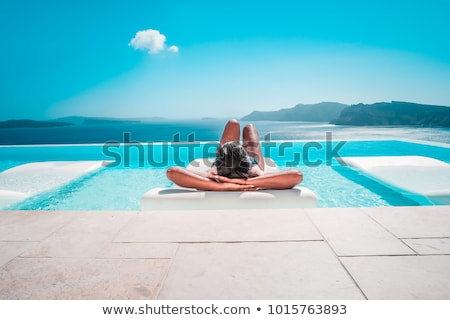 Luxury resort swimming pool. Beautiful woman tourist relaxing in holiday retreat on summer travel va Stock photo © galitskaya