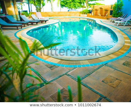 hotel patio with tables and chairs next to swimming pool stock photo © lypnyk2