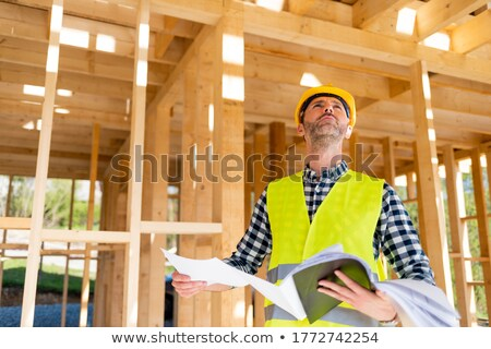 Foreman inspecting unfinished wooden house Stock photo © photography33