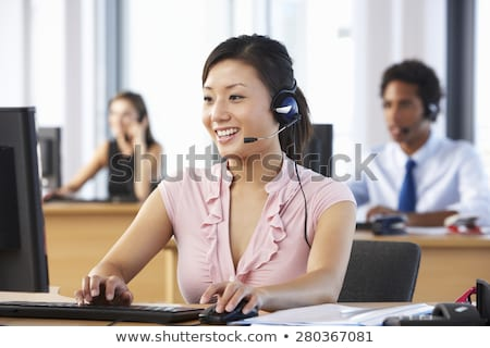 Smiling Asian call centre telephonist Stock photo © stryjek