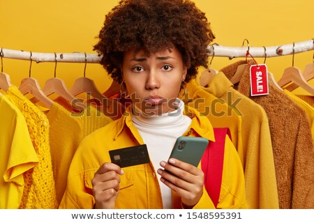 Woman is standing behind a clothes rack phoning in the shop Stock photo © wavebreak_media