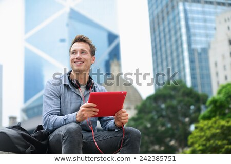 Smiling businessman looking at his tablet-pc Stock photo © stryjek