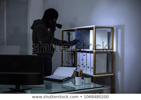 Thief in a balaclava stealing a file Stock photo © AndreyPopov