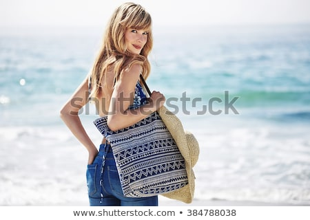 blond woman on beach smiling over shoulder stock photo © dash