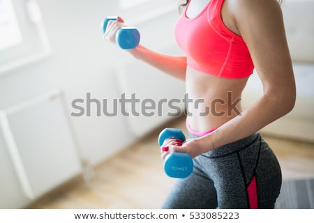 smiling young woman with dumbbell stock photo © wavebreak_media