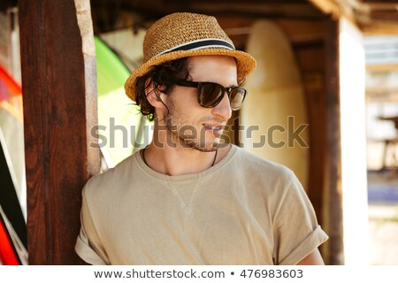 man in hat and sunglasses standing at the surf shack stock photo © deandrobot