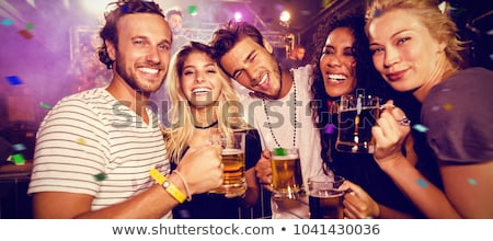 Happy friends toasting beer mugs at nightclub Stock photo © wavebreak_media