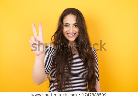 pretty cheerful brunette woman showing peace gesture while takin stock photo © deandrobot