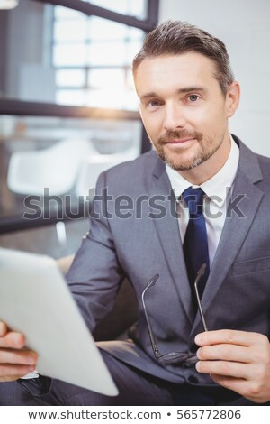 Businessman sitting on sofa with digital tablet and looking up Stock photo © wavebreak_media