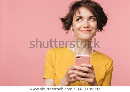Gyönyörű mosolyog lány fülhallgató okostelefon izolált Stock fotó © LightFieldStudios