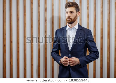 portrait of young man in black tuxedo fixing his links Stock photo © feedough