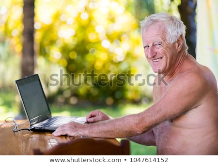 portrait of senior man working with laptop in outdoor without shirt stock photo © lopolo