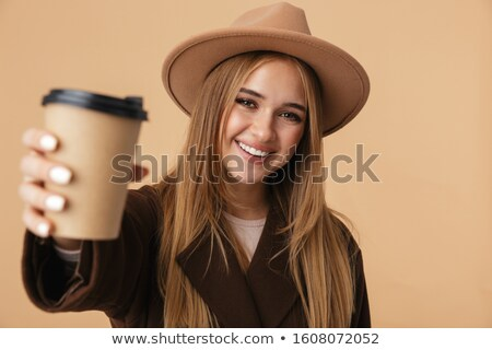image of charming woman holding takeaway coffee in paper cup and stock photo © deandrobot