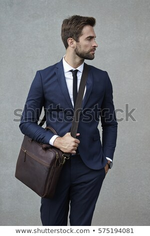 man holding briefcase and one hand in pocket looks away stock photo © feedough