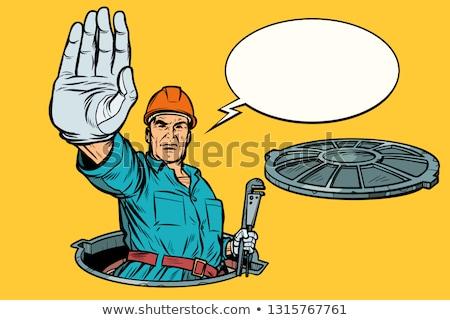 gesture stop. Plumber in the manhole Stock photo © studiostoks