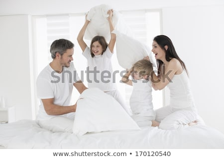 family with child having fun on bed with pillow fight stock photo © lopolo