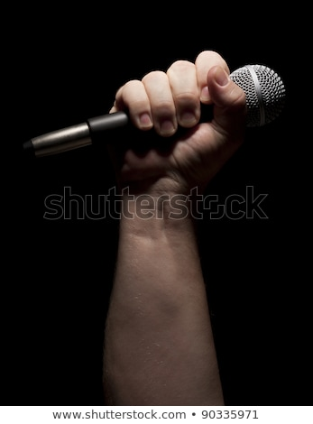 Vertical Microphone Clinched Firmly in Male Fist on a Black Back Stock photo © feverpitch